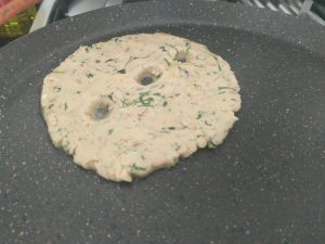 Thalipeeth cooking on hot tawa with oil in the centre and side