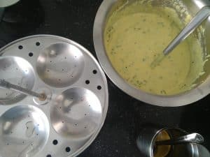 Grease Idli Plates to pour the idli batter