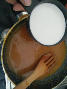 Adding the coconut milk to the banana puree and jaggery mix