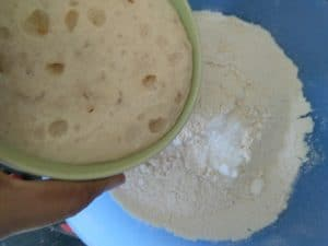 Adding the frothy yeast mixture to the whole wheat flour