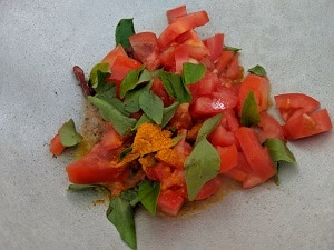 Tomatoes, curry leaves and turmeric powder for lemon rasam
