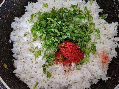 Leftover cooked rice is added with red chilli powder and coriander leaves for phodnicha bhat