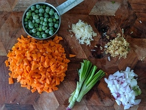 Ingredients chopped for the sweet corn soup - carrots, peas, scallions, ginger and garlic