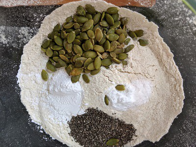Baking powder, baking soda, chia seeds and pumpkin seeds added to whole wheat flour