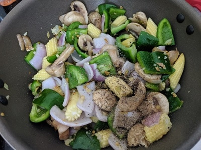 Seasoning the mixed vegetables with salt and pepper powder