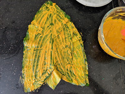 place one leaf above the other (upside down) and keep applying the besan batter on each alu leaf