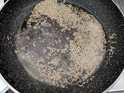 Pan with oil, mustard seeds, sesame seeds and hing as tempering for the alu vadi recipe