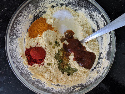 Adding spices and salt to the chickpea flour