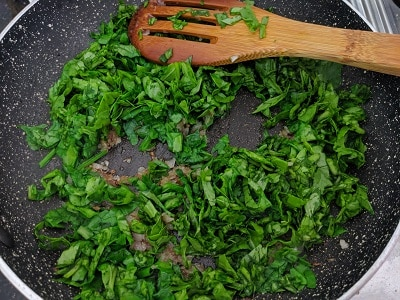 Finely chopped spinach leaves added to onions