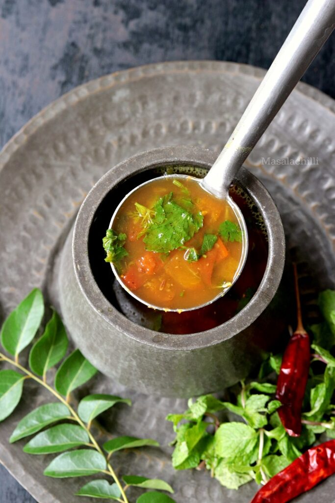 A ladle full of hot pudina rasam made with fresh mint leaves