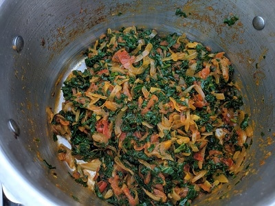 Kale cooking in onion tomato gravy with spices