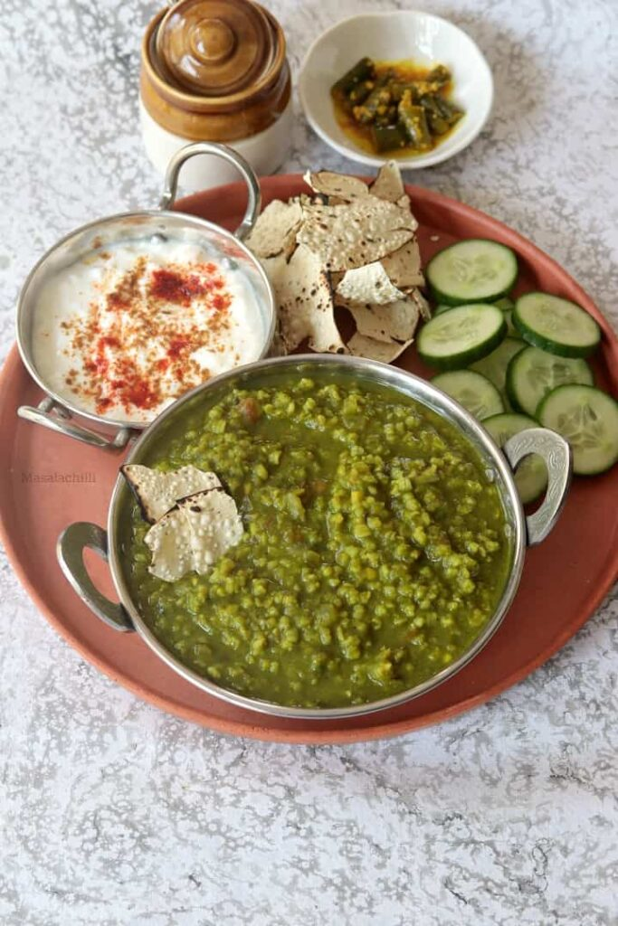Palak Khichdi served with curd, papad, salad and pickles