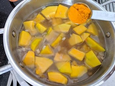 Adding turmeric powder to the pumpkins