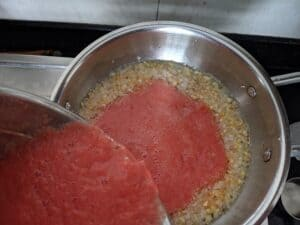 tomato puree cooking with olive oil, garlic and onion
