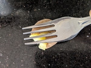 smashing the potatoes using a fork