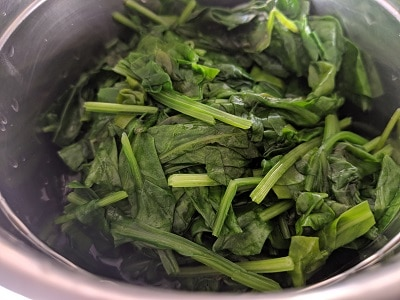 Grinding the cooked spinach leaves